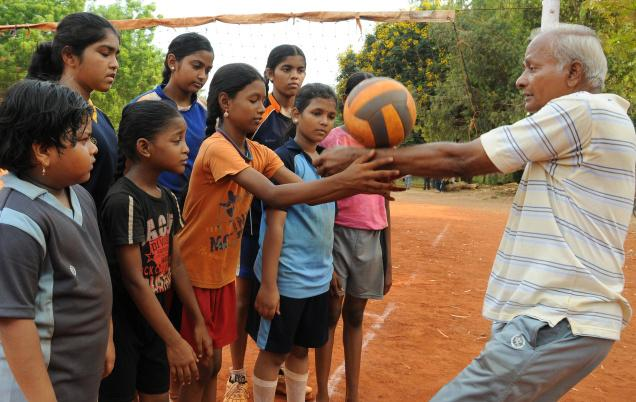 Koteswara Rao showing the basics to youngsters during the volleyball summer coaching camp at IGMC stadium in Vijayawada. / The Hindu