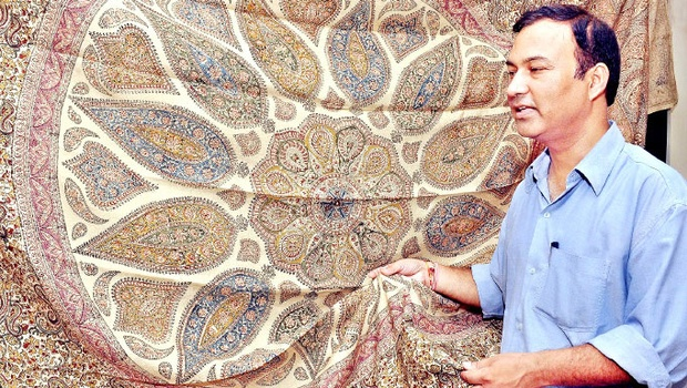 Deputy director of Weavers Service Centre Vishesh Nautiyal displaying the Kalamkari design printed on the linen bed sheet at the Centre in Vijayawada on Tuesday | Express Photo