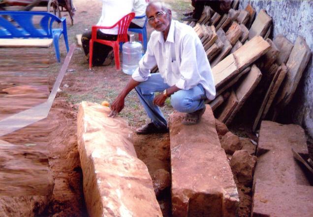 Archaeologist K. K. Venkateswaralu examines a 'thoranam', discovered near Bheemeswara Swamy Temple at Chebrolu in Guntur District./  Photo: By Arrangement / The Hindu