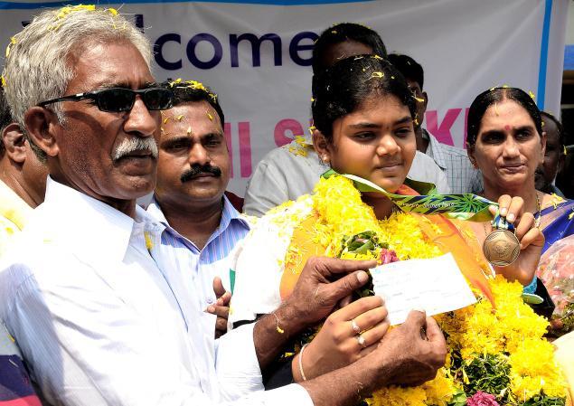 CBR Sports Academy chairman Chalasani Balaramaiah handing over a cheque for Rs. 5 lakh to Asian Games bronze medallist Jyothi Surekha on her arrival at Gannavaram Airport on Saturday. - Photo: Ch.Vijaya Bhaskar