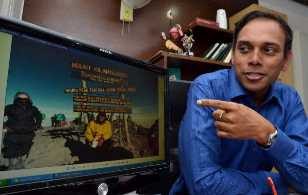 Endocrinologist Goutham Meher points out to a picture in which he is on the summit of Mount Kilimanjaro, the highest free standing mountain in the world. He is the first resident of Vijayawada to scale Mount Kilimanjaro. Photo: V. Raju / The Hindu
