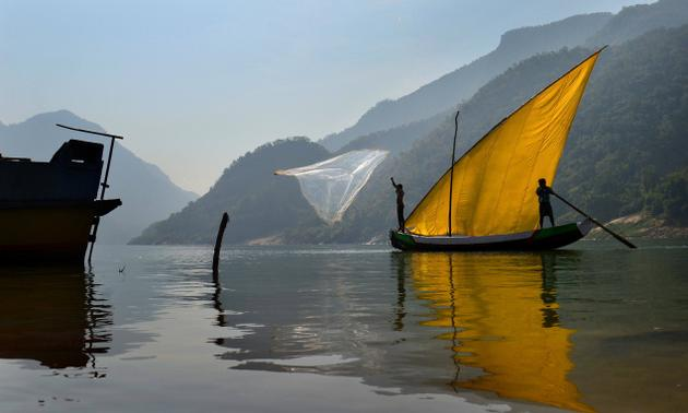 Fishermen casting their nets in the river; Tourist boat approaching the shore. Photo: K.R. Deepak