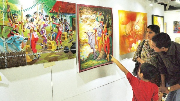 A family has a look at the paintings on display at an art exhibition organised by the Vijayawada Art Society at the Culture Centre in Vijayawada on Thursday | P Ravindra Babu