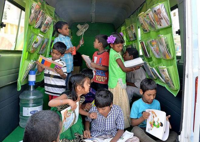 Reaching out:Children from Jalaripeta near the Fishing Habour reading books at the mobile library of the WNS Cares Foundation in Visakhapatnam on Monday.K.R. DeepakK_R_DEEPAK