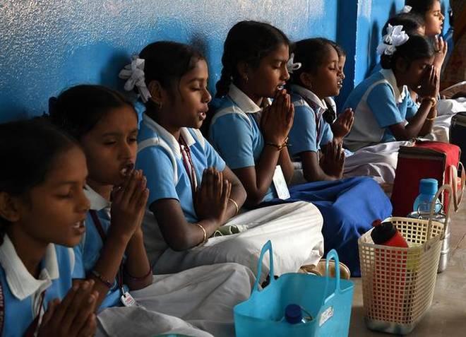 Imbibing values Children saying their prayers before taking lunch at Chukkapalli High School at Adavinekkalam. | Photo Credit: V RAJU.