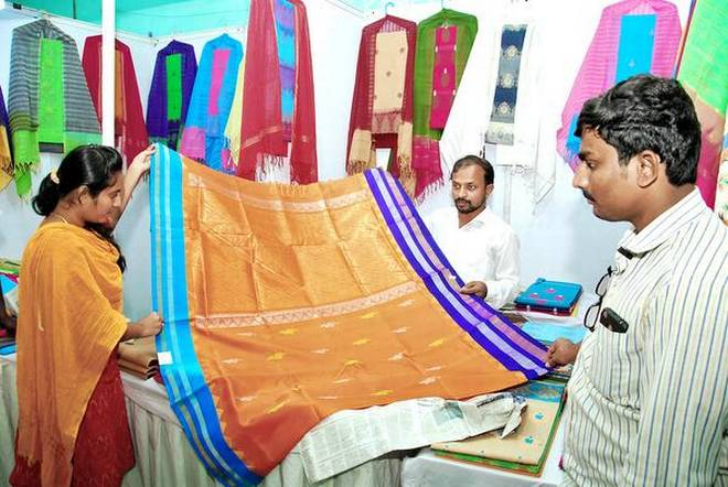 A weaver displays a colourful sari at a handloom expo in Ongole on Thursday.