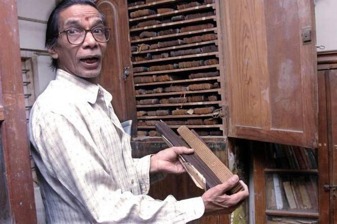 Rare collection: A file photo of a staff member showing the palm leaf manuscripts in the library. | Photo Credit: C.V.SUBRAHMANYAM