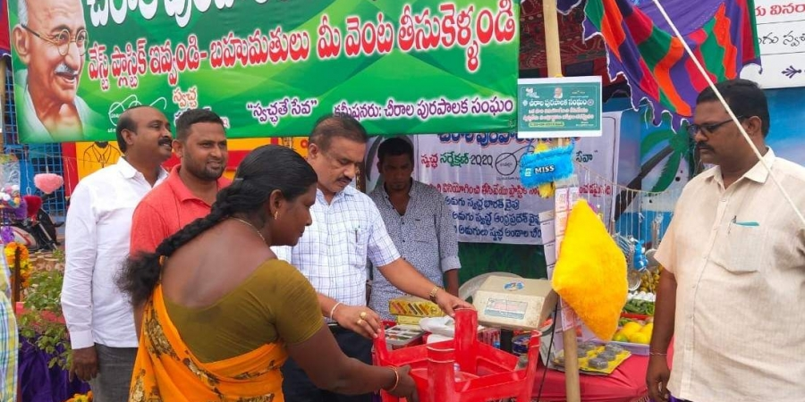 Chirala Municipal commissioner Ramachandra Reddy along with staff members inspecting the weighing of plastic waste materials at the newly established 'Waste Plastic Exchange Shop'(Photo | EPS)